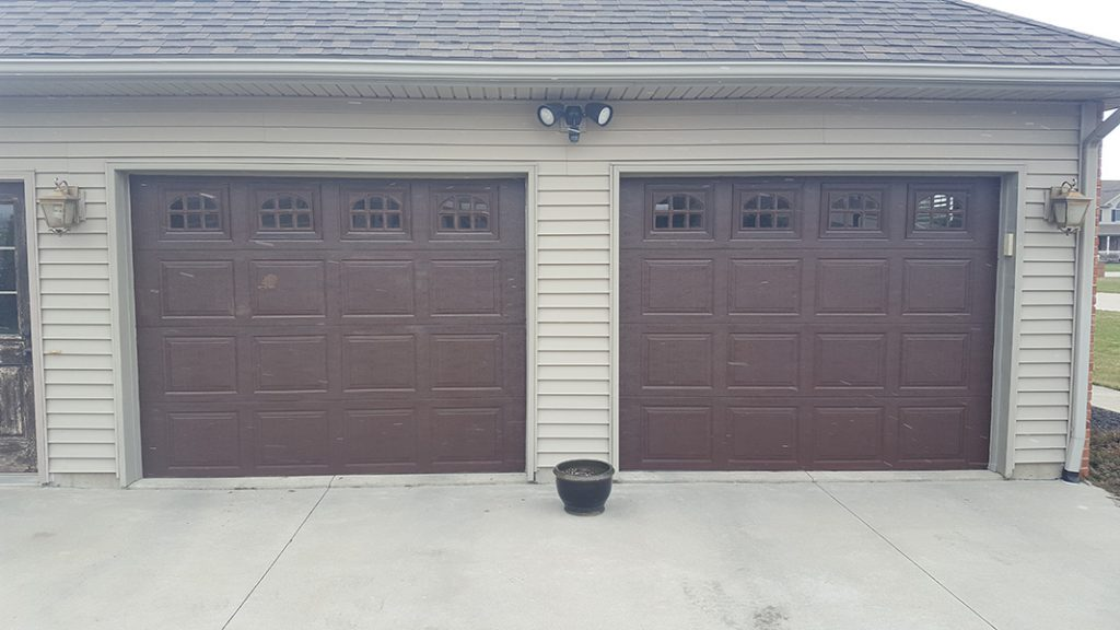 Photo of garage with two brown overhead doors